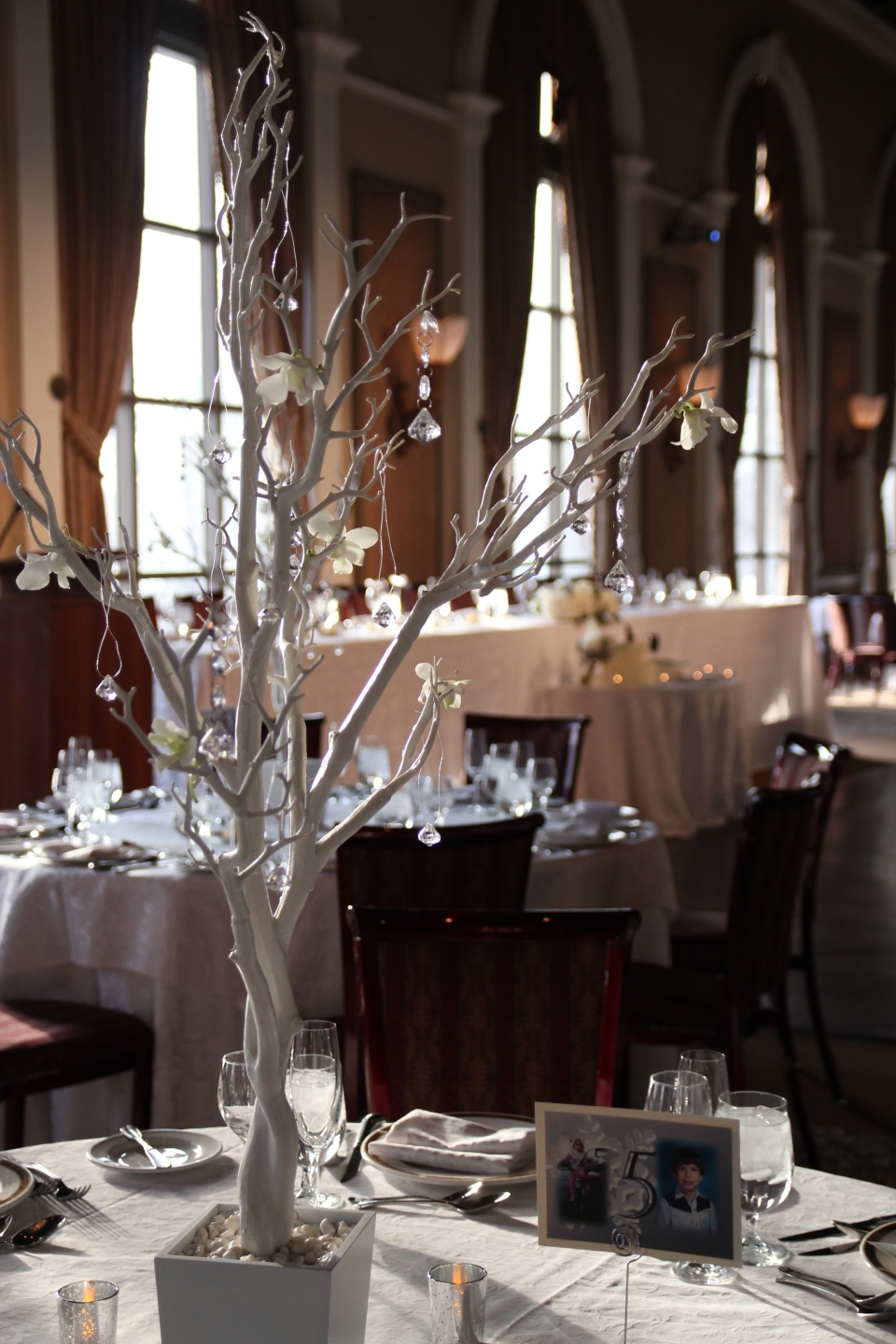 White trees with crystal drops and white orchids for the tall centerpieces