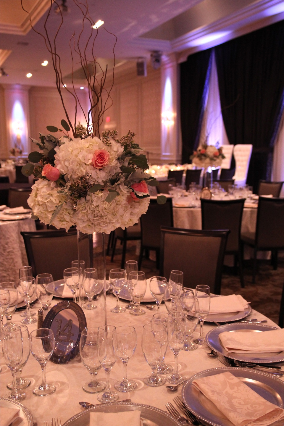 Tall centerpieces of hydrangea, roses, waxflower with curly willow