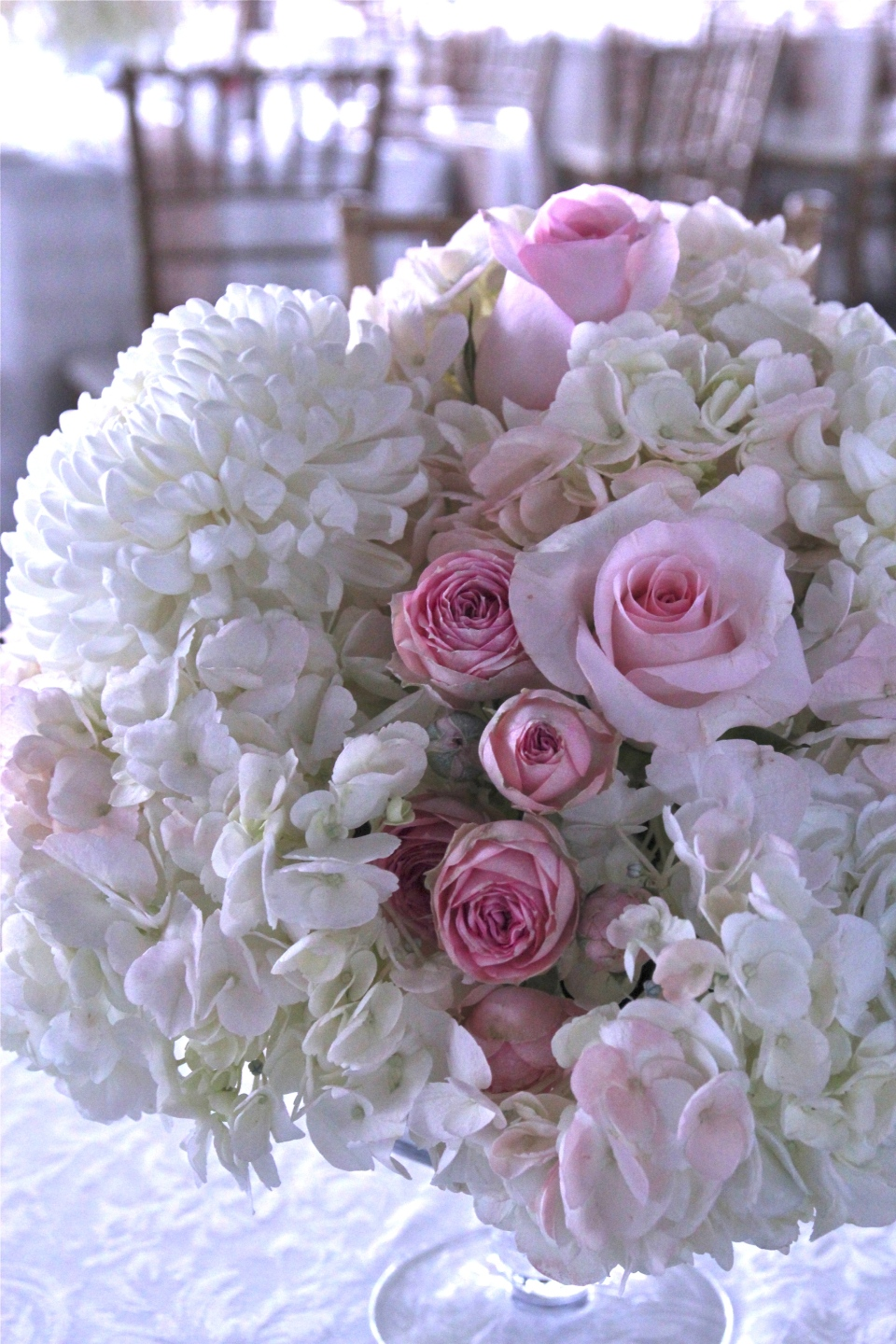 Blush and white centerpieces of hydrangea, roses, spray roses and mums.