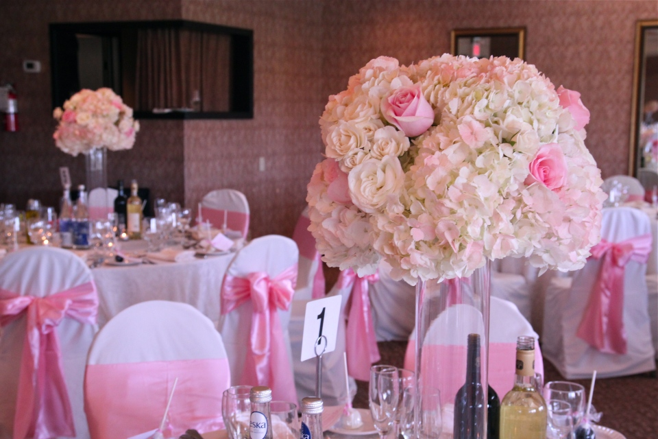 Tall centerpieces of white hydrangea and pink roses.
