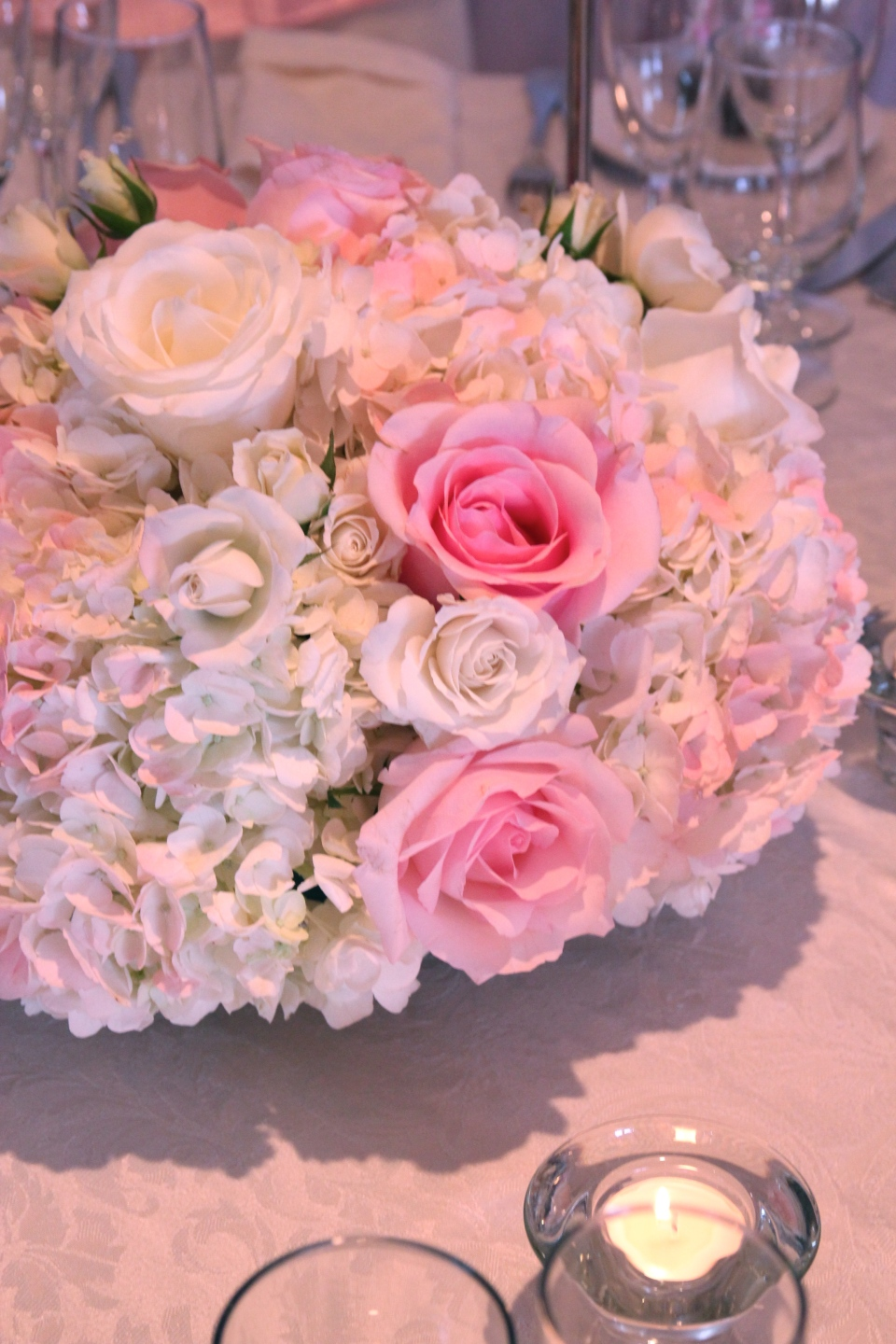Low pink centerpieces of hydrangea and roses.