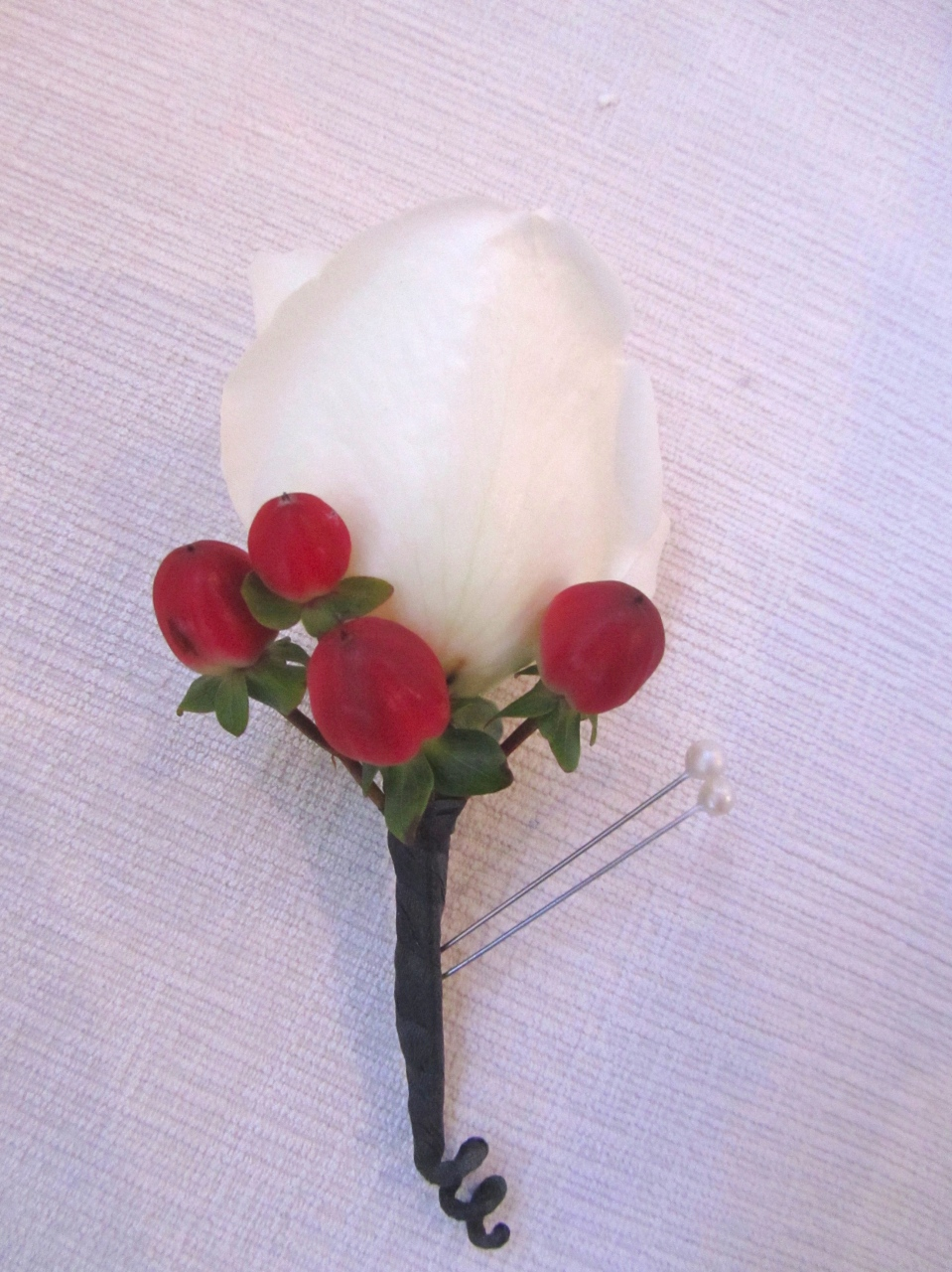 White rose and red berry boutonniere