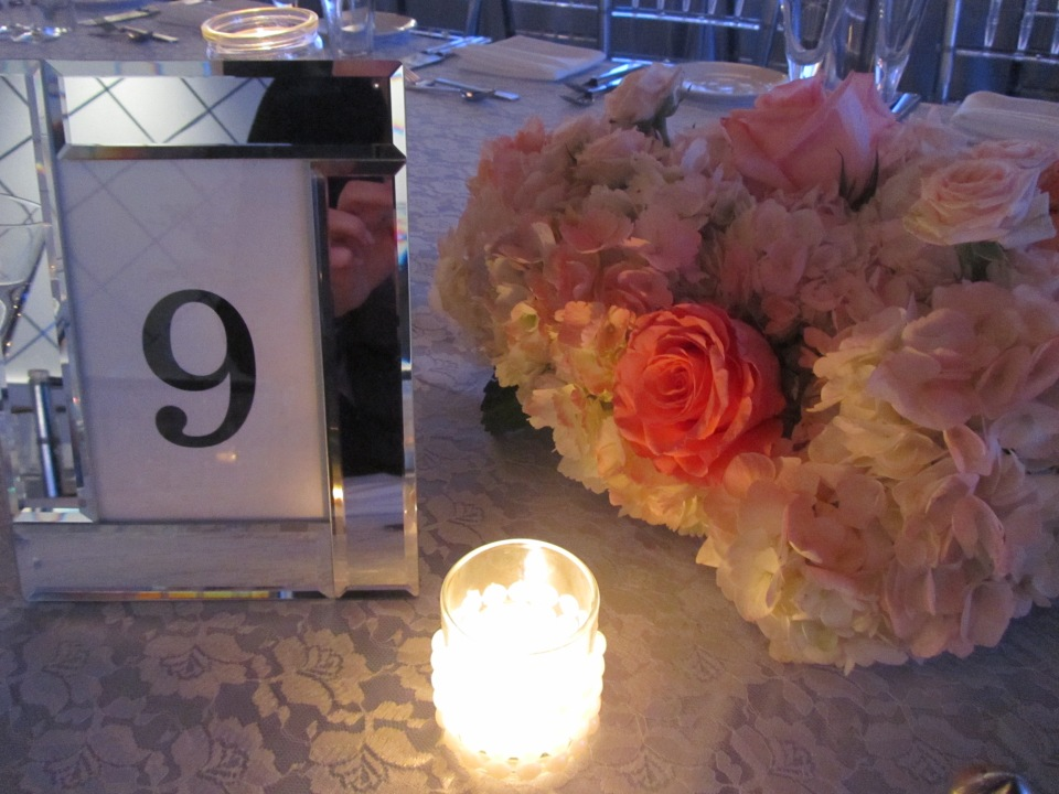 Coral and peach roses with hydrangea for low centerpieces.