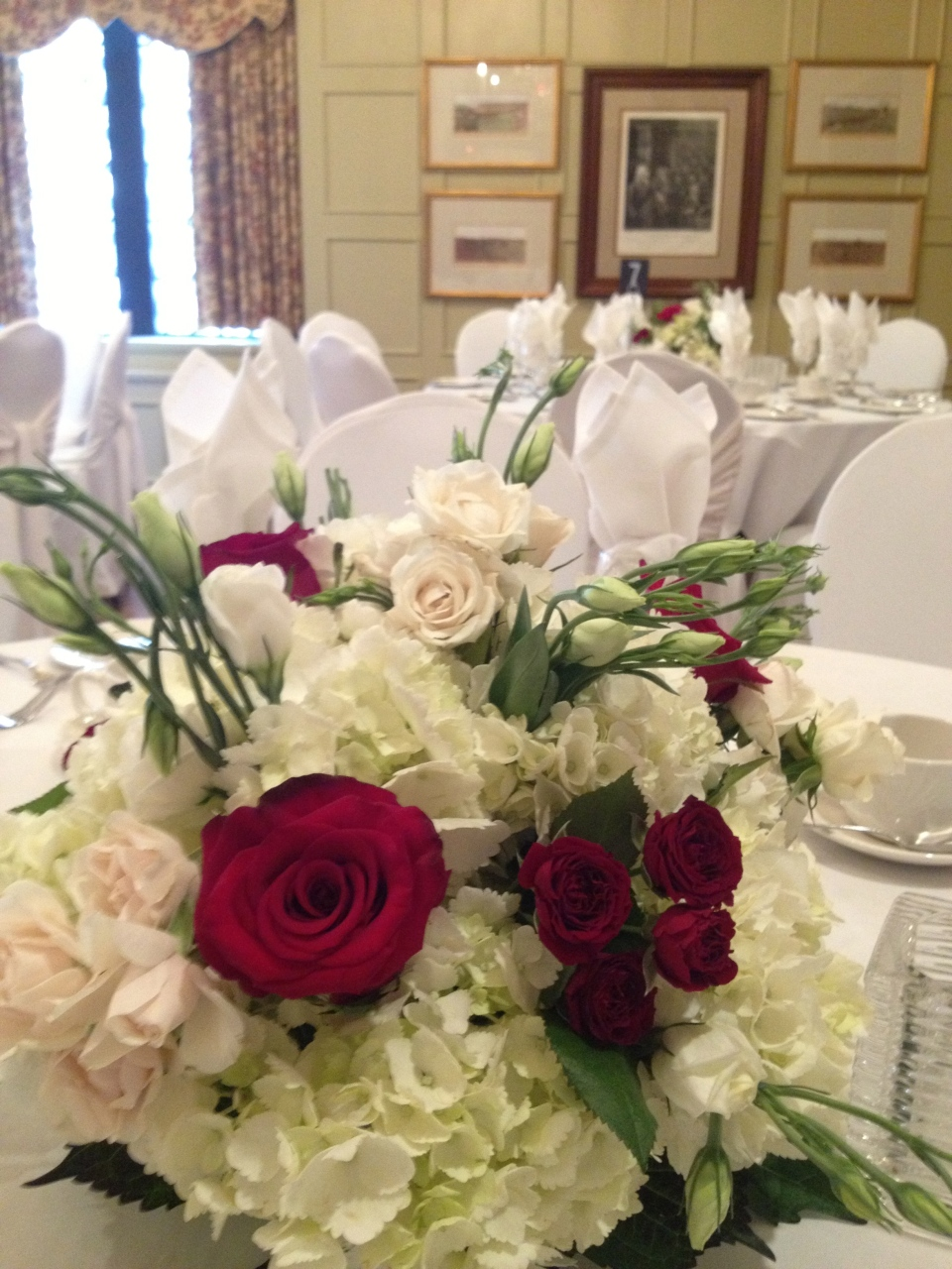 Garden inspired low centerpiece of hydrangea, roses, spray roses and lisianthus.