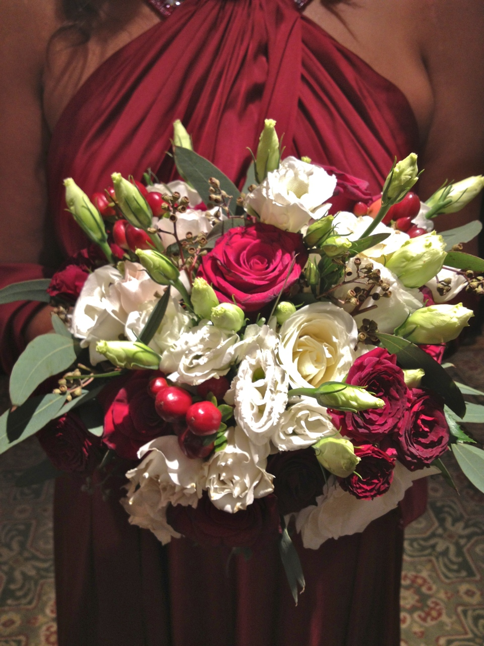 Cranberry and white bouquet of roses, lisianthus, berries and greens