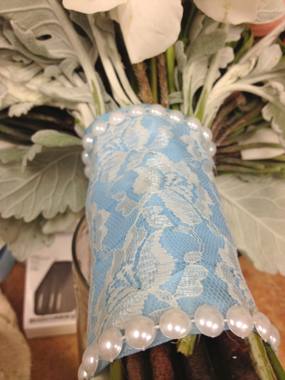 Ivory lace overlay over light blue satin trimmed with pearls for the bridal bouquet.