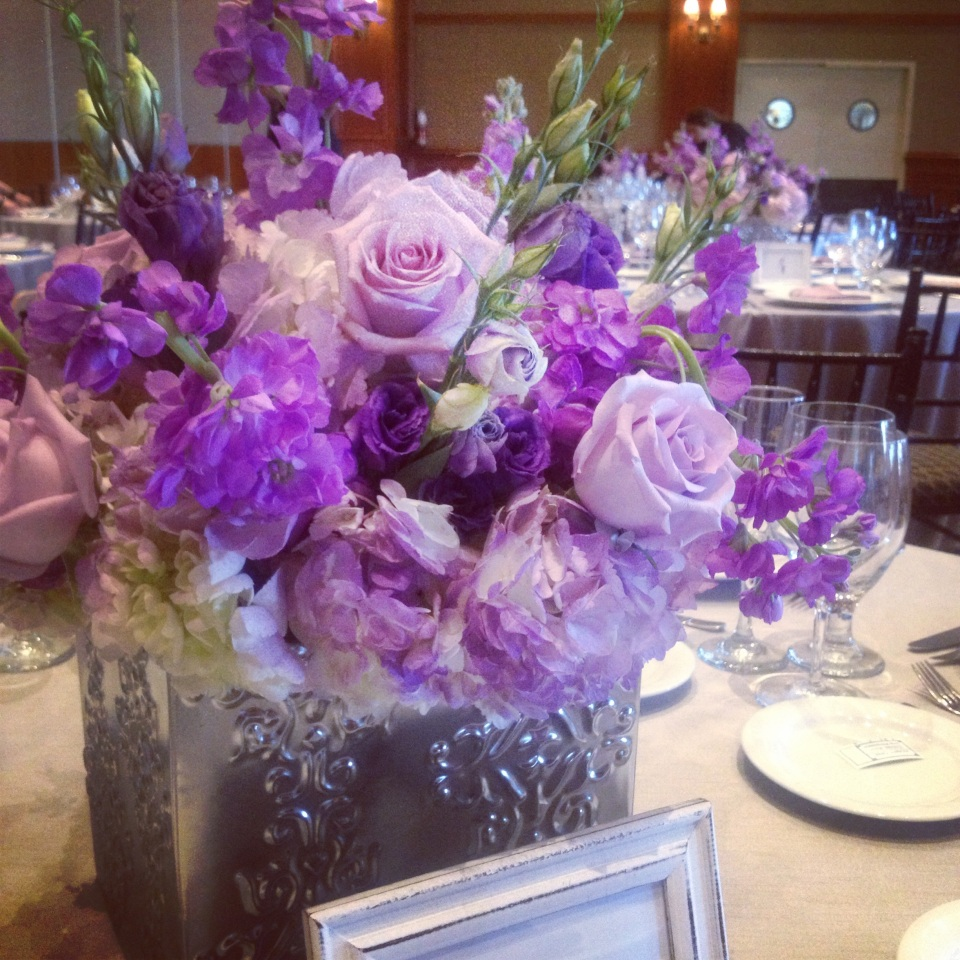 Centerpiece of purple roses, stock, lisianthus and hydrangea