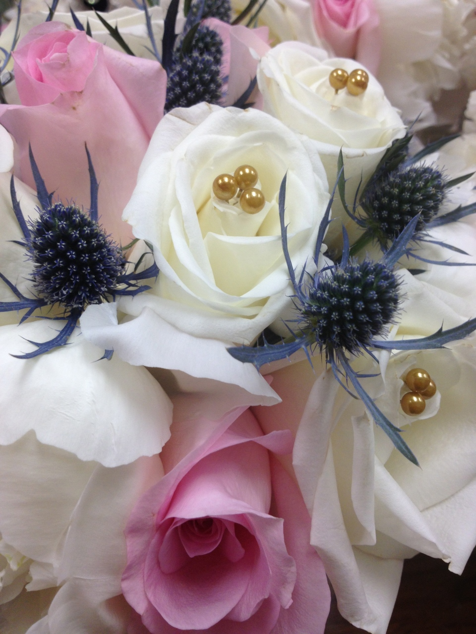Blush and ivory roses with blue thistle