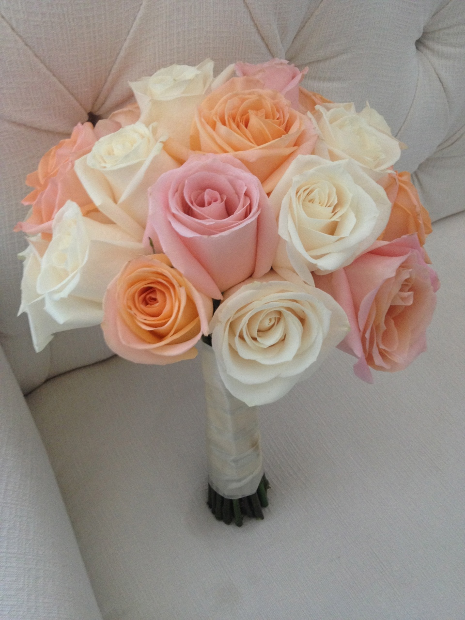 Bridal bouquet of ivory, blush and peach roses.
