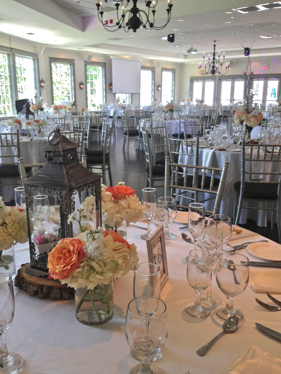 Lantern centerpieces surrounded by roses and hydrangea