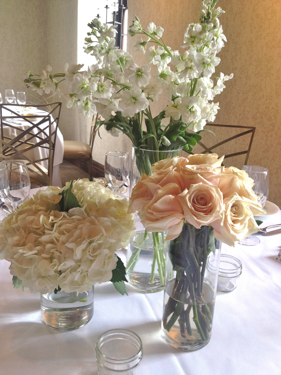 Trio of stock flower, roses and hydrangea was clustered on the round tables.