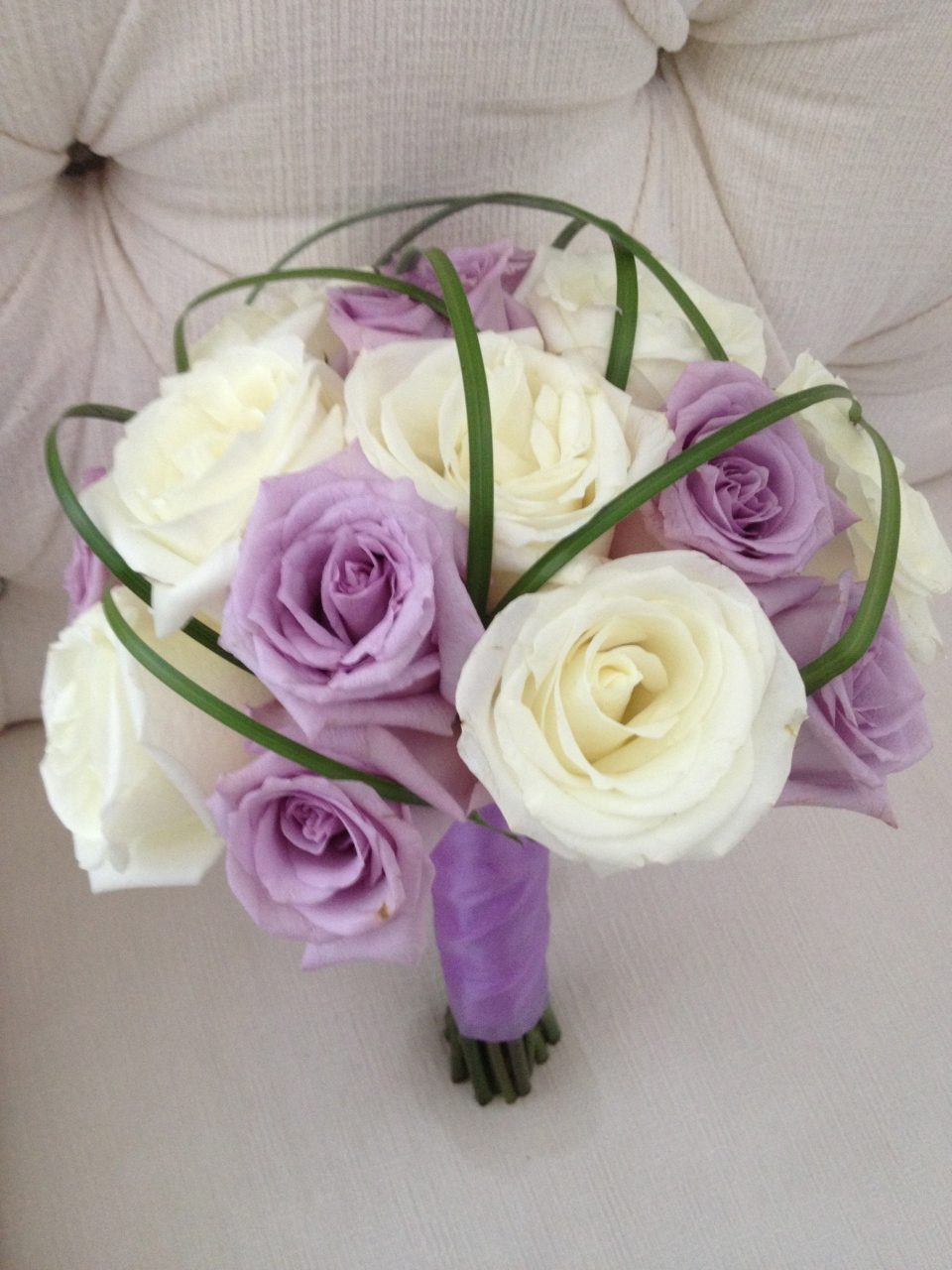 Bridesmaids bouquet of lavender and ivory roses with sculpted bear grass
