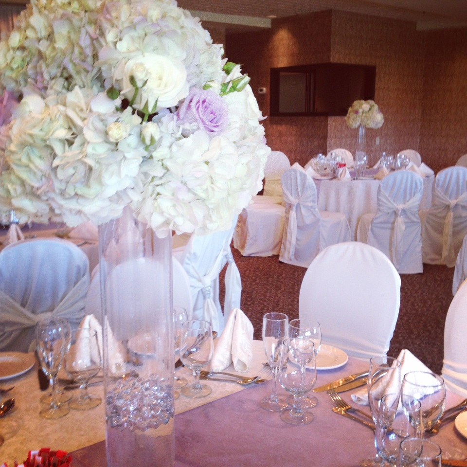 Tall centerpieces of hydrangea and roses matched perfectly with the lavender table runners