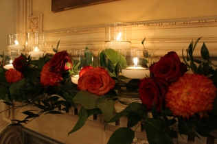 Orange and Red Roses and Greenery Mantle Decor